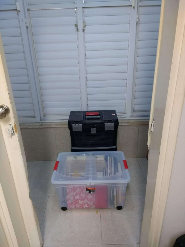 ארגז פלסטיק אחד שקוף ושני ארגזי כלים במרפסת שירות.